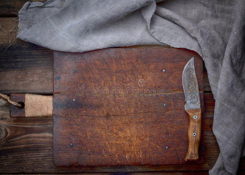 muy vieja tabla de cortar de madera marr?n vac?a con la manija fotos de archivo