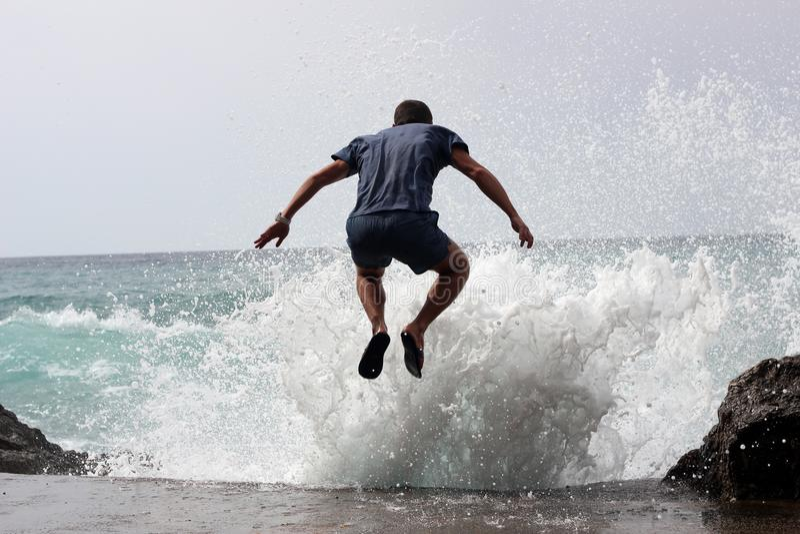 31/5000 muzhchina prygayet V vsplesk volny Mann, der in ein Wellenspritzen springt stockfotografie