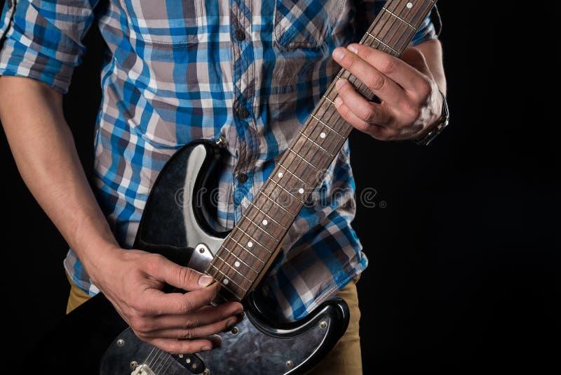 Muziek en art. Elektrische gitaar in de handen van een gitarist, op een zwarte geïsoleerde achtergrond Het spelen gitaar Horizont royalty-vrije stock foto's