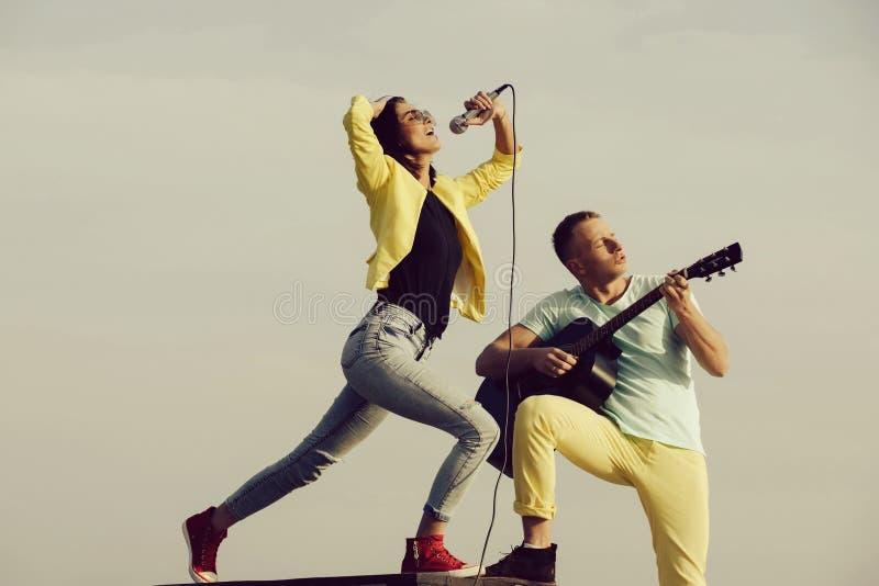 Muziekband van de mens en vrouw met gitaar en microfoon royalty-vrije stock afbeelding