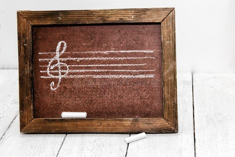 Muziekcijfer en g-sleutel in krijt op een schoolraad die wordt getrokken stock foto