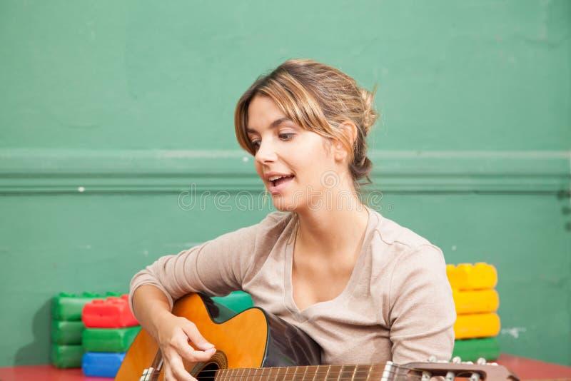 Muziekleraar in de kleuterschool royalty-vrije stock afbeeldingen