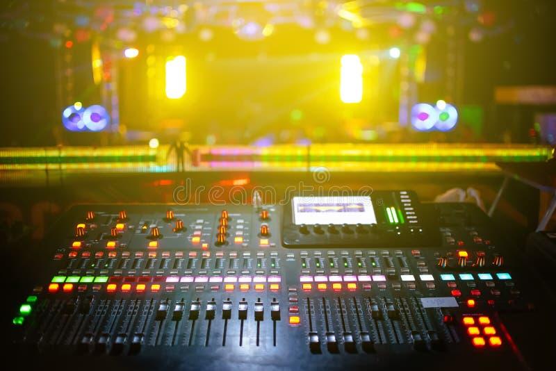 Muziekmixer met stadium, vage overlegachtergrond, geel licht stock afbeelding