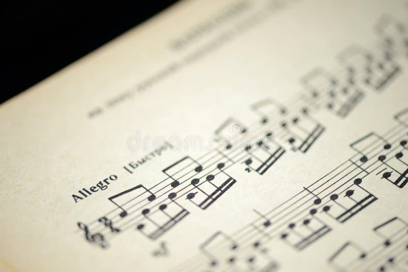 Muzikaal tempo ` Allegro ` in een oud muzieknotitieboekje royalty-vrije stock afbeelding