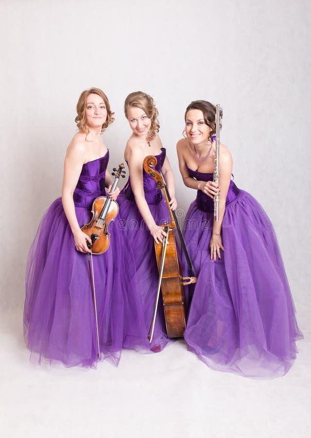 Muzikaal trio in purpere kleding stock afbeeldingen