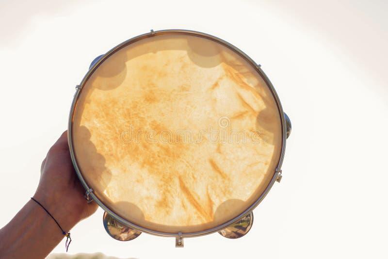 Muzikale instrumententamboerijn of pandeiro op een achtergrond van de hemel bij zonsondergang stock foto's