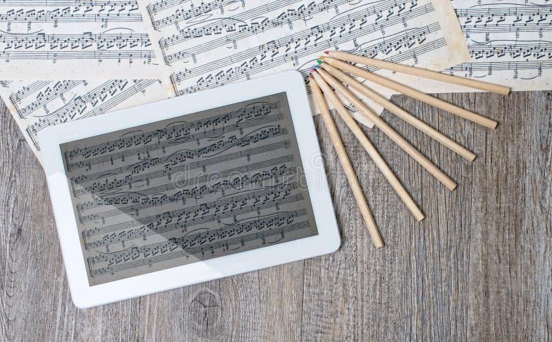 Muzikale scores met een digitale tablet stock afbeelding