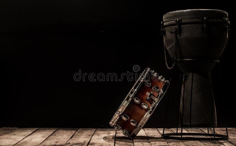 Muzikale slaginstrumenten op zwarte trommel als achtergrond Bongo en strik vector illustratie