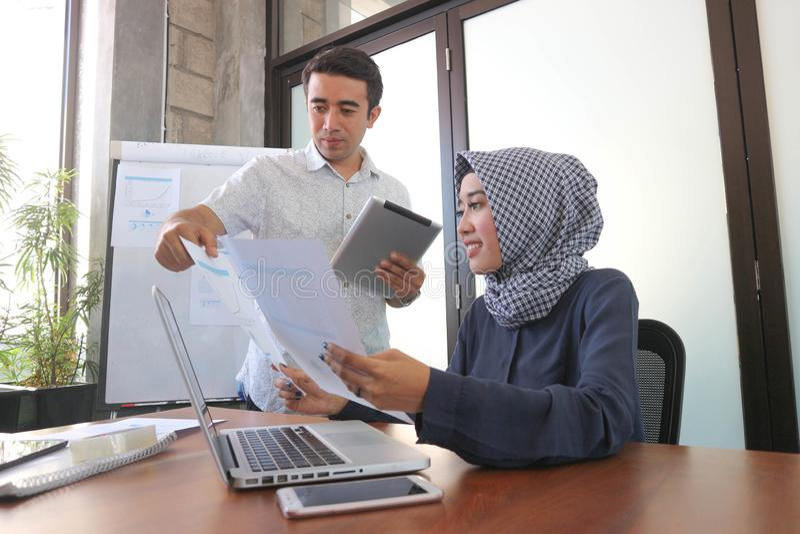 Muzułmański bizneswoman i przystojny mężczyzna pracuje wraz z laptop pastylką i papierowymi pobliskimi okno z białą deską pokazuj obraz royalty free