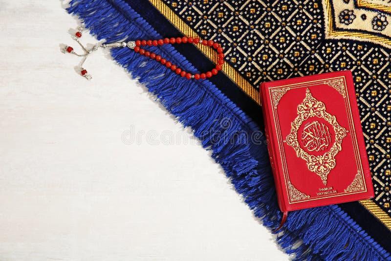 Muzułmańscy modlitewni koraliki, koran, dywanik i przestrzeń dla teksta na lekkim tle, obraz royalty free