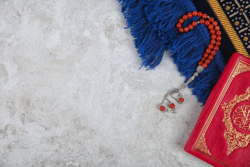 Muzułmańscy modlitewni koraliki, koran, dywanik i przestrzeń dla teksta na popielatym tle, zdjęcia stock