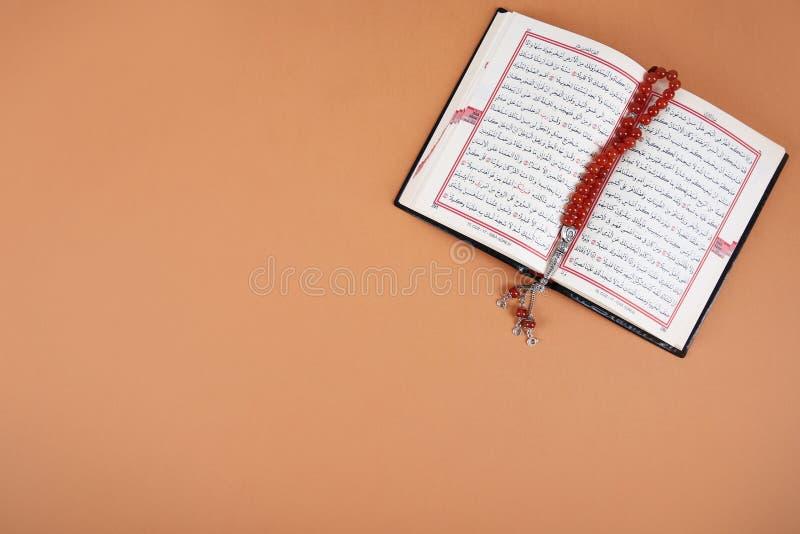 Muzułmańscy modlitewni koraliki, koran i przestrzeń dla teksta na koloru tle, obraz stock