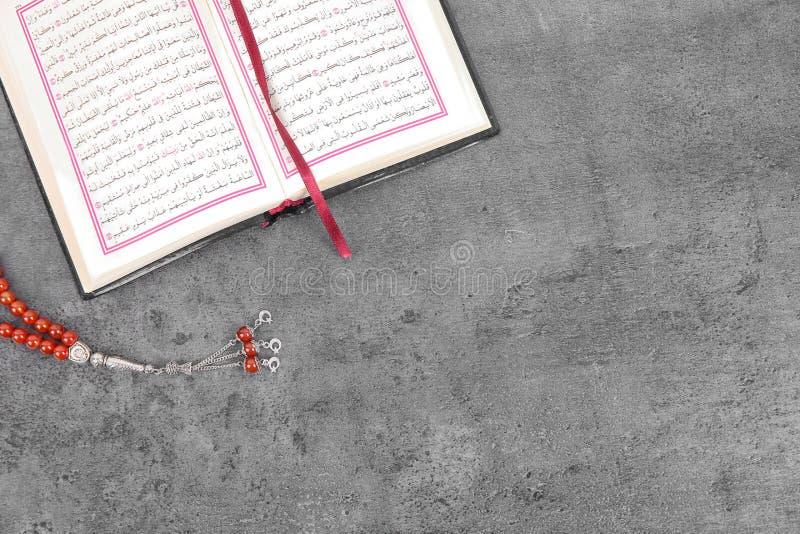 Muzułmańscy modlitewni koraliki, koran i przestrzeń dla teksta na popielatym tle, zdjęcia stock