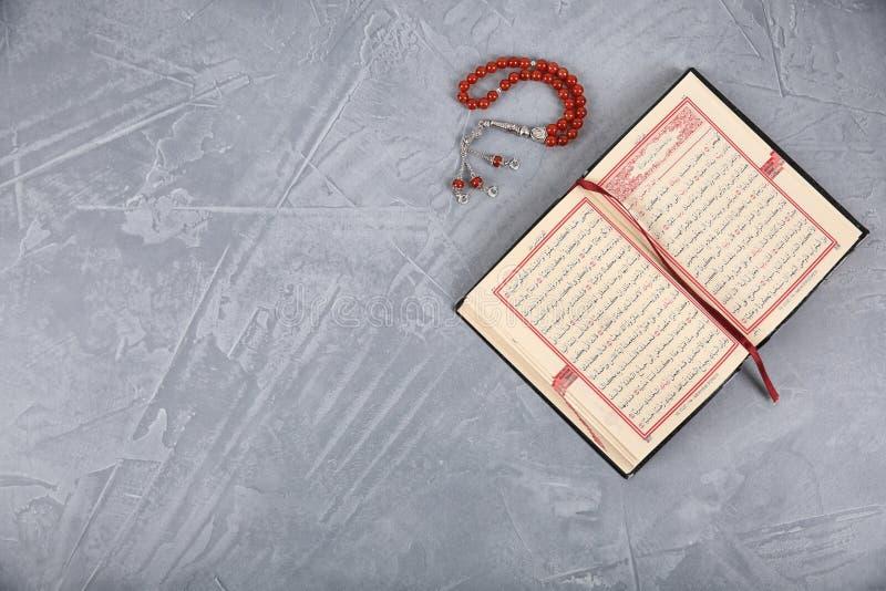 Muzułmańscy modlitewni koraliki, koran i przestrzeń dla teksta na popielatym tle, fotografia stock