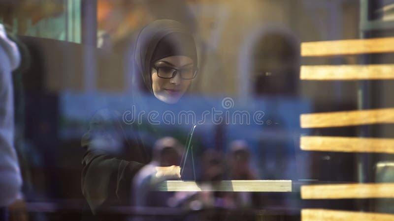 Muzułmańska dama w tradycyjnym ubraniowym gawędzeniu na zakładki obsiadaniu w kawiarni, nowoczesne życie obrazy stock