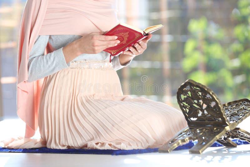Muzułmańska kobieta czyta Koran na modlitewnej macie indoors obrazy royalty free
