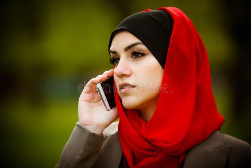 Muzułmańska kobieta opowiada na telefonie i używa technologię Muzułmańska kobieta używa mądrze telefon obrazy royalty free