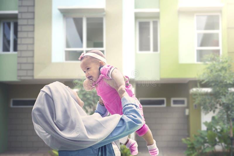 Muzułmańska kobieta podnosi jej dziecka przy outdoors fotografia stock