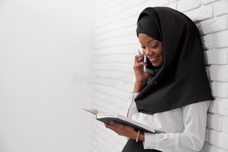 Muzułmańska kobieta stoi opierać przy ścianą, opowiada przy telefonem fotografia stock