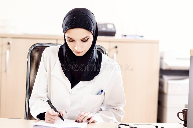 Muzułmańska kobiety lekarka wypełnia medyczne kartoteki obraz stock