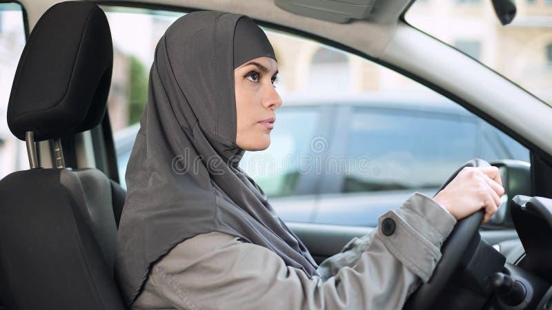 Muzułmański damy obsiadanie w samochodowym przyglądającym tylni widoku lustrze, napędowa licencja, transport zdjęcie royalty free