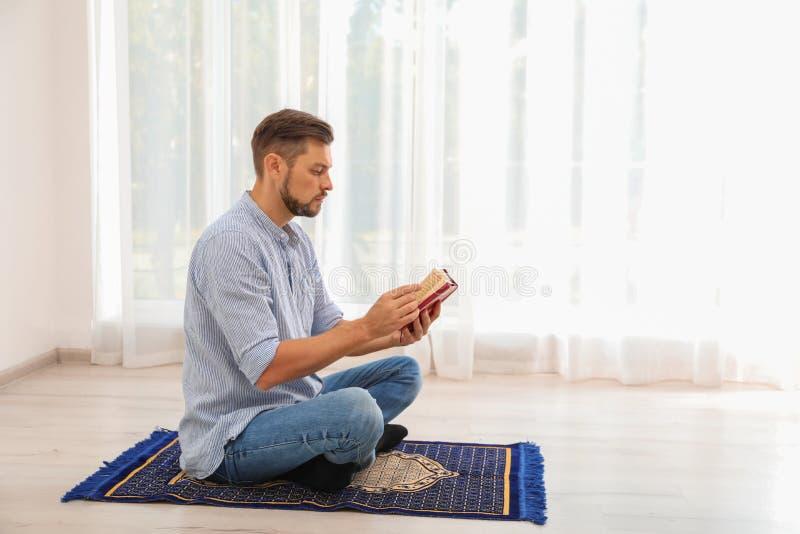 Muzułmański mężczyzna czyta Koran na modlitewnym dywaniku obrazy stock