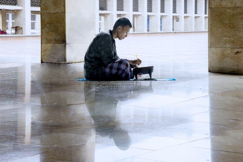 Muzułmański mężczyzna czyta koran w meczecie zdjęcie stock