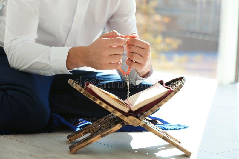 Muzułmański mężczyzna ono modli się indoors z Koran i misbaha obrazy royalty free