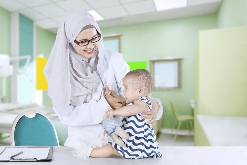 Muzułmański pediatra egzamininuje małego dziecka fotografia stock