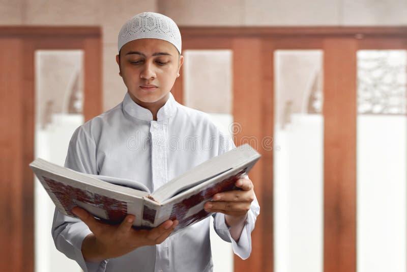 Muzułmańskiego mężczyzna czytelniczy koran wśrodku meczetu obrazy royalty free