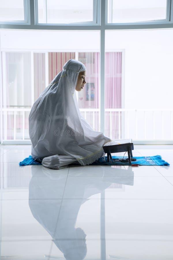 Muzułmańskiej kobiety czytelniczy koran blisko okno fotografia stock