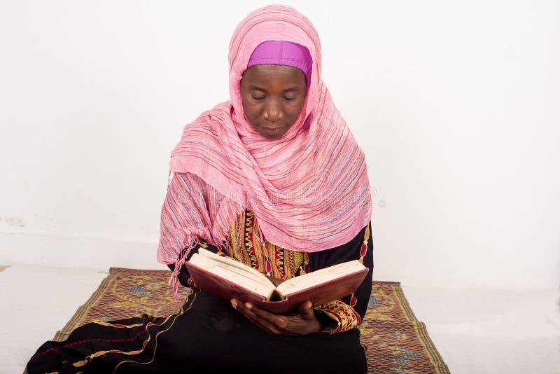 Muzułmańskiej kobiety siedzący modlenie czyta Koran obraz stock