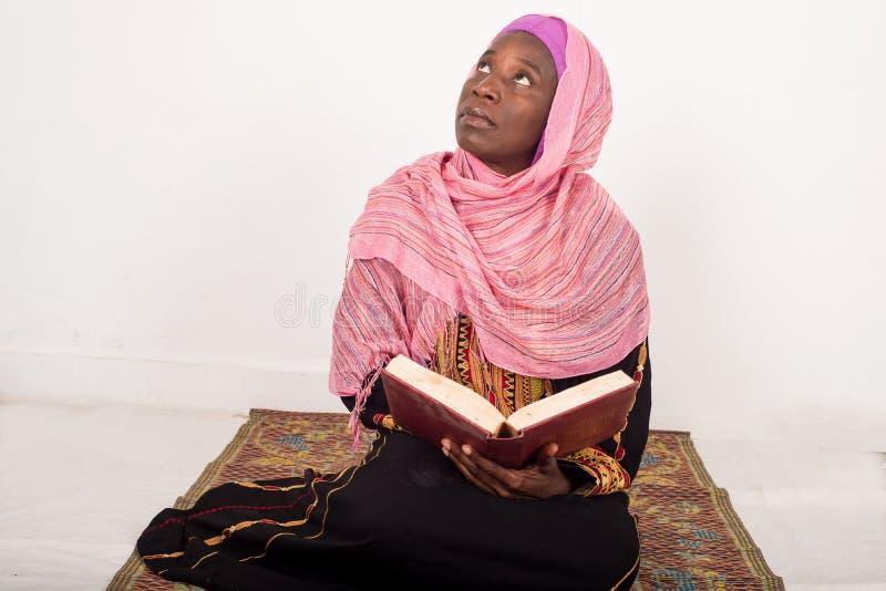 Muzułmańskiej kobiety siedzący modlenie czyta Koran obrazy stock