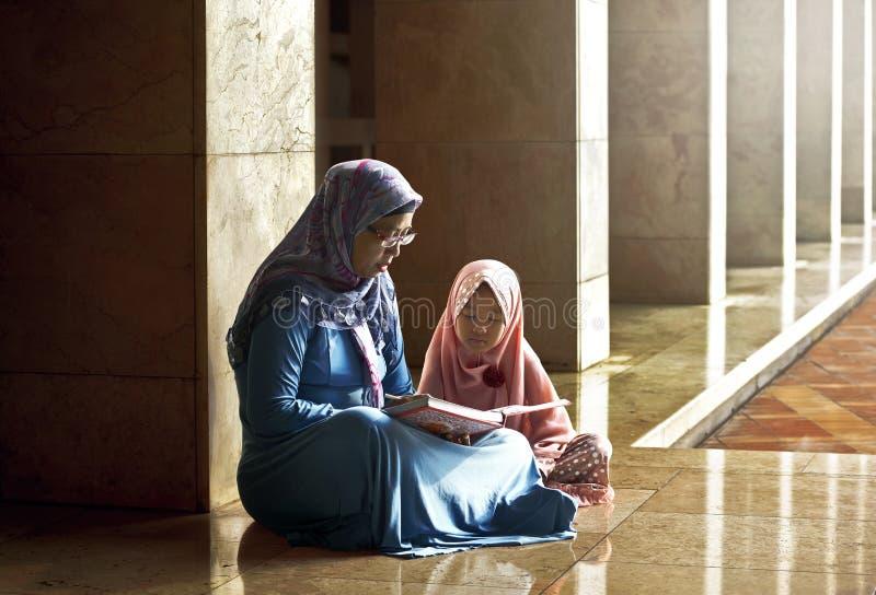 Muzułmanin matka uczy jej córce czytelniczego koran zdjęcie royalty free