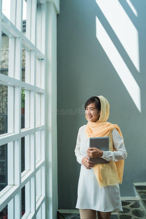 Muzu?ma?ska kobieta jest ubranym hijab u?ywa? pastylka komputer osobistego obraz stock
