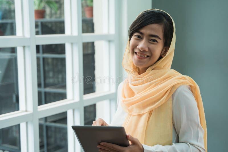 Muzu?ma?ska kobieta jest ubranym hijab u?ywa? pastylka komputer osobistego obrazy stock