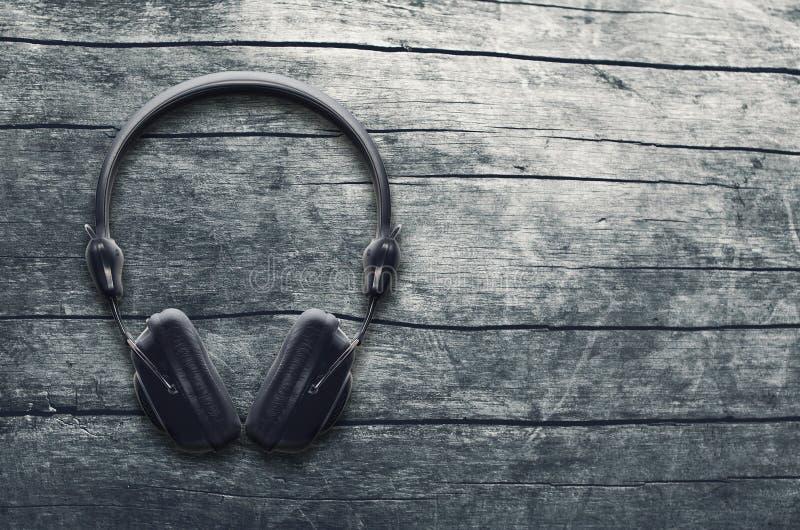 Muzyczny grunge tło, czarni hełmofony na drewnianym stole obrazy stock
