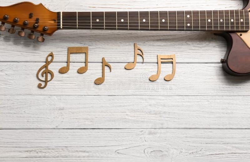 Muzyk notatki i gitary szyja na drewnianym tle obraz royalty free