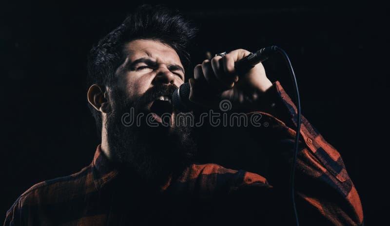 Muzyk z brodą i wąsy zaświecał światłem reflektorów Talentu przedstawienia pojęcie Muzyk, piosenkarza śpiew w hali koncertowej, k obraz royalty free