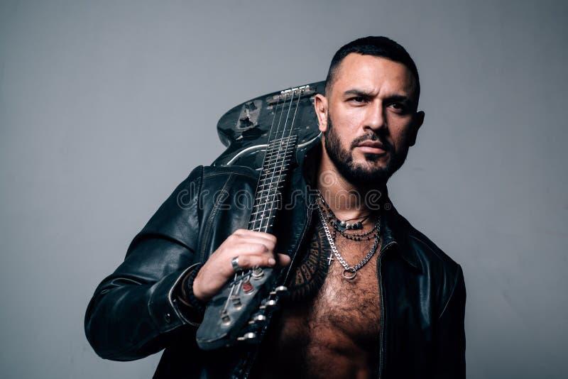 Muzyka dla Dj pojęcia Elegancki brutalny mężczyzna z brodą, tatuażu mienia gitara Seksowny spojrzenie męski model uczy? si? i obraz stock