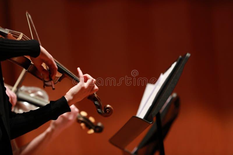 muzyka klasyczna Skrzypaczki w koncercie Nawleczony, violinistCloseup bawić się skrzypce podczas symfoni muzyk obrazy royalty free