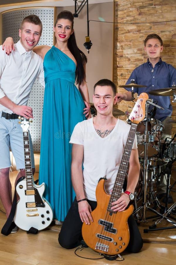 Muzykalna grupa trzy faceta i jeden dziewczyna w studiu nagrań fotografia royalty free