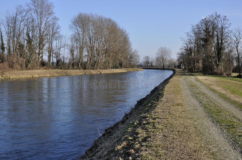 Muzza bank in winter country. Foreshortening of important artificial canal in winter country , shot in bright light on lombardy plains stock photography