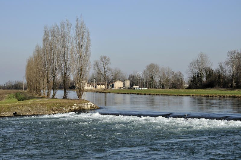Muzza canal fall in winter. Foreshortening of important artificial canal in winter country , shot in bright light on lombardy plains royalty free stock photos
