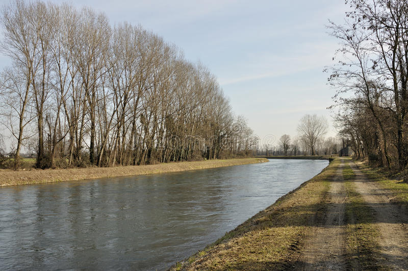 Muzza canal in winter country. Foreshortening of important artificial canal in winter country , shot in bright light on lombardy plains stock photography