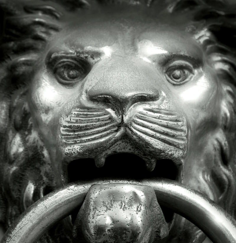 Muzzle lion. Close up of a handle door sculpture of a muzzle lion in black and white stock photography
