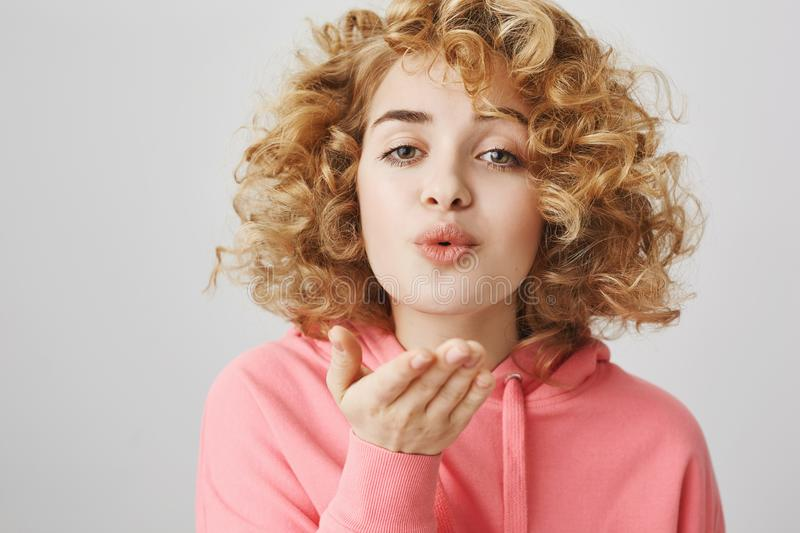 Mwah for all my besties. Portrait of good-looking cute curly-haired girl puckering with lovely expression and holding. Palm near lips to blow kiss at camera royalty free stock images