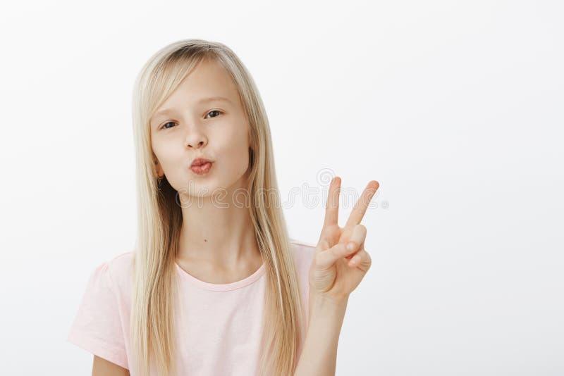 Mwah till mina anhängare, uppdaterat stag Stående av den trendiga säkra unga flickan med naturligt ganska hår, hopfällbara kanter royaltyfri foto