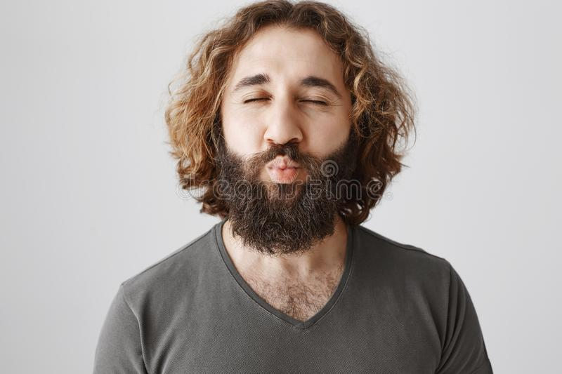 Mwah to all of you. Friendly passionate eastern man with curly hair and beard puckering lips and closing eyes, desiring stock image