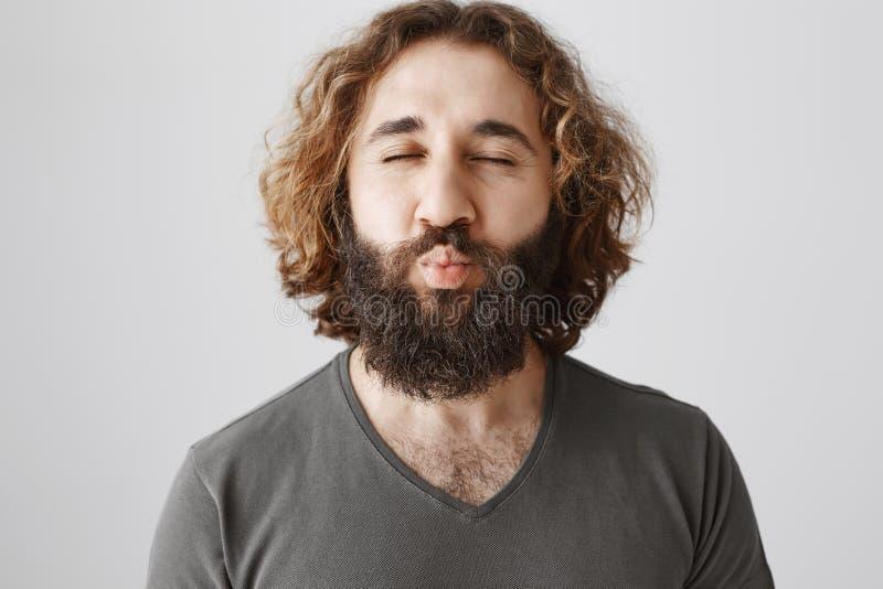 Mwah a usted Hombre del este apasionado amistoso con el pelo rizado y barba que frunce los labios y los ojos del closing, deseand imagen de archivo